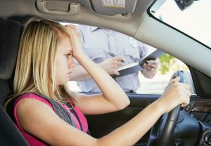 An unhappy teenage girl receiving a speeding ticket from a police officer.