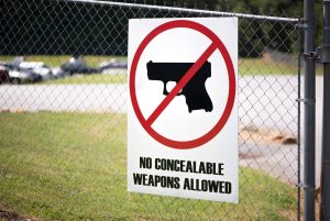 horizontal photograph of a sign showing a no gun zone area