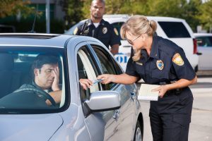 A mature female law enforcement officer stands by a vehicle she has stopped and takes the driver's license from a middle aged man